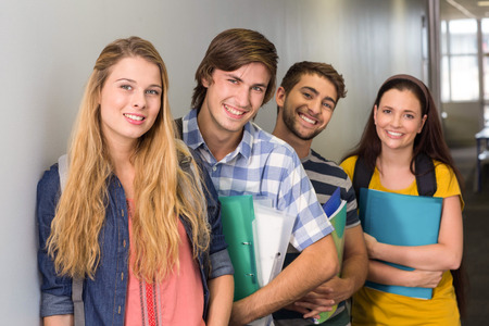higher intelligence: Portrait of happy students holding folders at college corridor