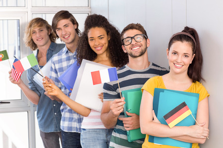higher intelligence: Portrait of happy college students holding flags Stock Photo