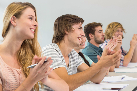 Side view of students clapping hands in classroom Stock Photo