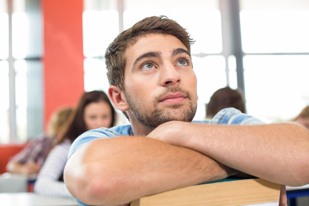 Thoughtful male student with books in the classroom photo