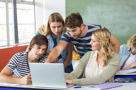 Groep studenten die laptop in klaslokaal met behulp van