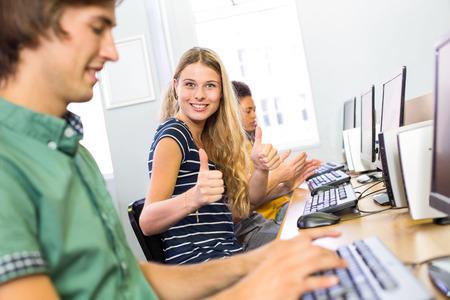 コンピュータ ・ クラスでジェスチャーの親指を女子学生の肖像画