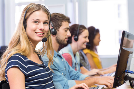Side view of students using headsets in computer class photo