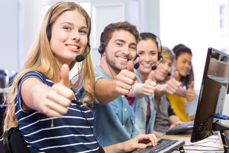 Portrait of students using headsets while gesturing thumbs up in computer class photo