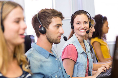 Side view portrait of students using headsets in computer class photo