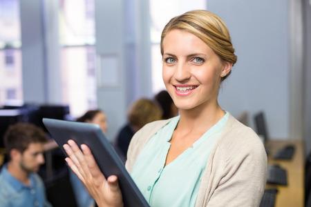 internet class: Portrait of happy female teacher using digital tablet in computer class Stock Photo