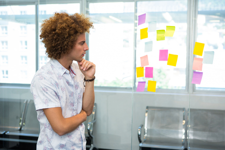 adhesive  note: Creative young businessman looking at adhesive note in office Stock Photo