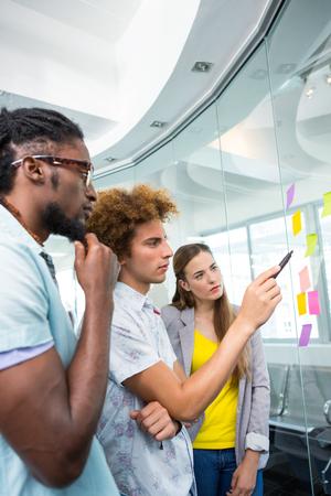 profesionistas: Personas creativas del asunto que señala en las notas adhesivas en la oficina