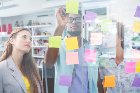 creative writing: Creative business team writing on adhesive notes in office Stock Photo