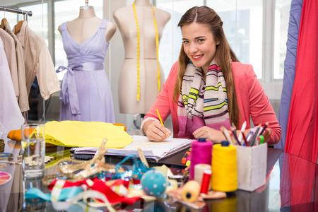 Portret van aantrekkelijke vrouwelijke mode-ontwerper schetsen aan tafel Stockfoto