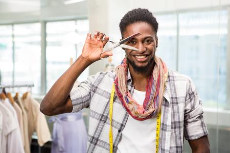 fashion industry: Portrait of happy male fashion designer holding scissors Stock Photo