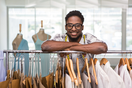male fashion: Portrait of male fashion designer leaning on rack of clothes