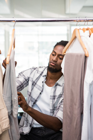 clothes rack: Portrait of male fashion designer looking at rack of clothes Stock Photo
