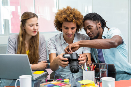 digital design: Creative young business people looking at digital camera at office desk
