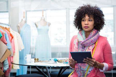 디지털 태블릿을 사용하여 매력적인 여성 패션 디자이너