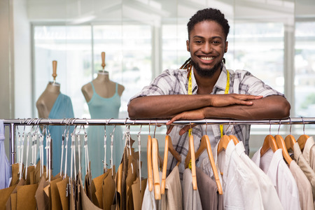 business fashion: Portrait of male fashion designer leaning on rack of clothes