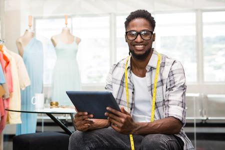 Portret van glimlachende vertrouwen mannelijke mode-ontwerper met digitale tablet