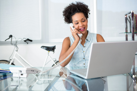 attractive office: Beautiful casual young woman using telephone and laptop in office Stock Photo