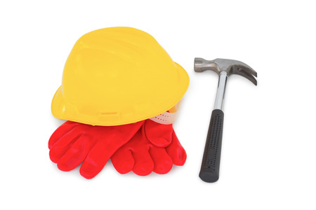 protective work wear: Yellow hardhat with protective gloves and hammer on white background Stock Photo