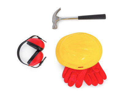 protective gloves: Yellow hardhat with protective gloves, earmuffs and hammer on white background Stock Photo