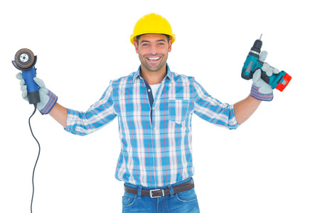 power tools: Portrait of manual worker holding power tools on white background