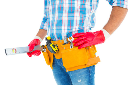 protective work wear: Midsection of handyman holding spirit level on white background Stock Photo