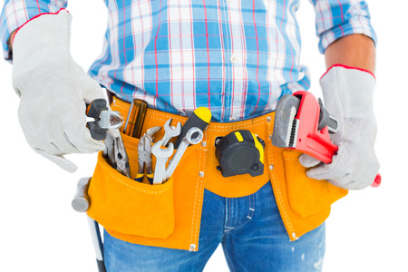 protective work wear: Midsection of handyman holding hand tools on white background