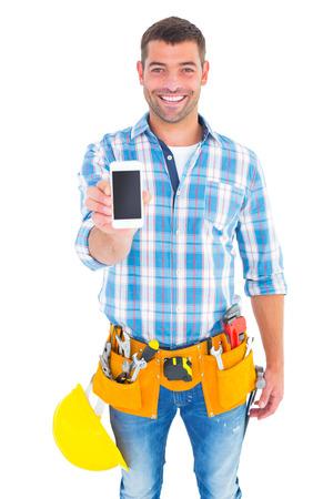 man holding: Portrait of smiling handyman showing mobile phone on white background Stock Photo
