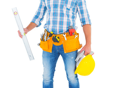 spirit level: Midsection of manual worker holding spirit level on white background