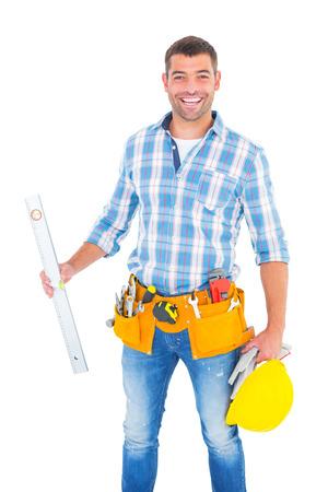 spirit level: Portrait of smiling manual worker holding spirit level on white background