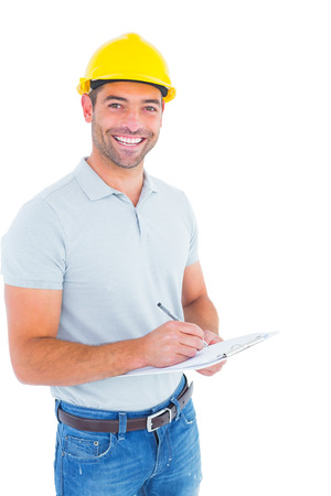 yellow helmet: Portrait of smiling male supervisor writing on clipboard on white background