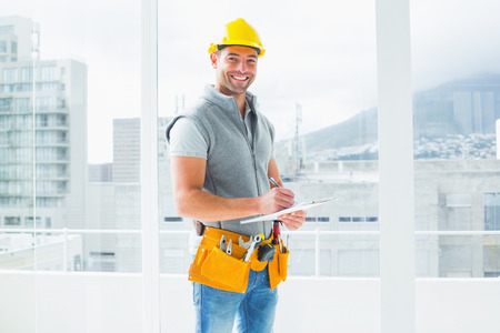 Portret van glimlachende handarbeider schrijven op het klembord in de bouw Stockfoto