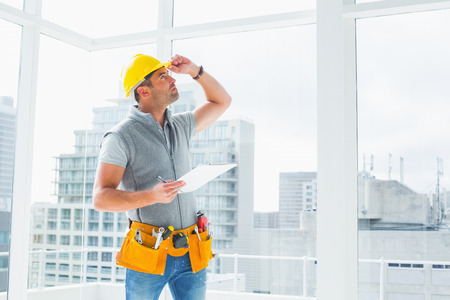 maintenance: Handyman holding clipboard while inspecting building Stock Photo