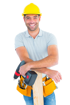 power drill: Portrait of smiling male carpenter with power drill and plank on white background