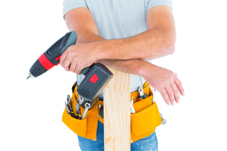 power drill: Midsection of male carpenter with power drill and plank on white background Stock Photo