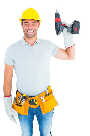 power drill: Portrait of handyman wearing tool belt while holding power drill on white background