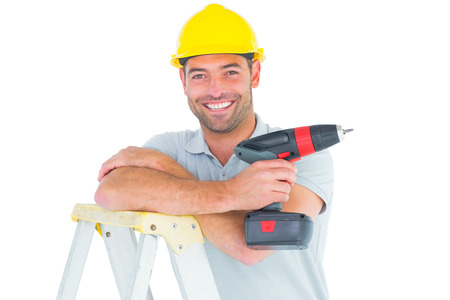 power drill: Portrait of male technician holding power drill on ladder over white background