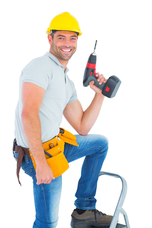 power drill: Portrait of confident handyman holding power drill while climbing ladder on white background Stock Photo