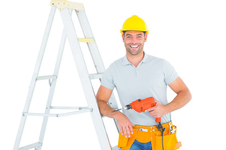 Portrait of happy handyman with power drill leaning on ladder over white background photo