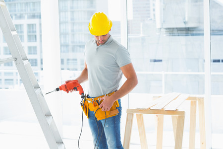 Repairman with drill machine standing by ladder in building photo