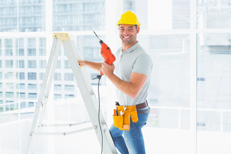 climbing ladder: Portrait of repairman with drill machine climbing ladder in building Stock Photo