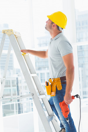 Side view of handyman with drill machine climbing ladder in building photo