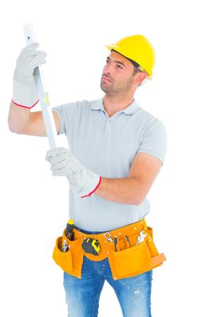 spirit level: Handyman examining spirit level on white background