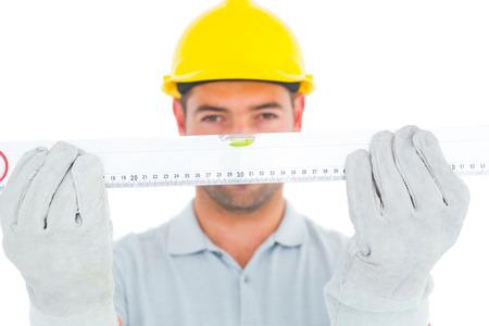 spirit level: Portrait of handyman holding spirit level on white background