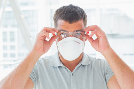 protective eyewear: Portrait of confident handyman wearing protective eyewear and mask at site