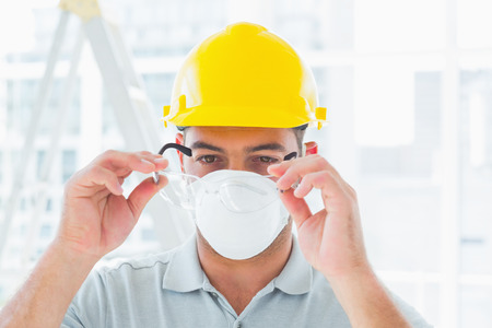 protective eyewear: Confident handyman wearing protective eyewear at construction site Stock Photo