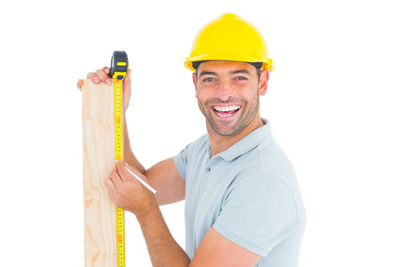 Male construction worker using measure tape to mark on wooden plank on white background photo