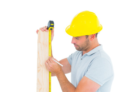 Male carpenter using measure tape to mark on wooden plank on white background photo