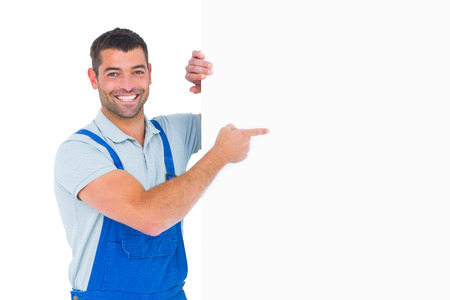 Portrait of smiling repairman in overalls pointing at placard over white background Imagens - 38186216