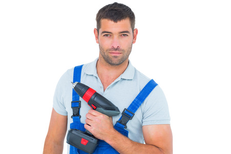 power drill: Portrait of confident male carpenter holding power drill on white background